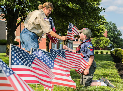 Clarksville Boy Scout Troop 4010 Committee Chair Holly Rupprecht, left, hands her son Drake Rupprecht, 9,  a Webelos Scout of the same troop, a flag to be placed in the front lawn of the Clark County Courthouse building on Friday. They put in place 160 flags. Staff Photo By Josh Hicks