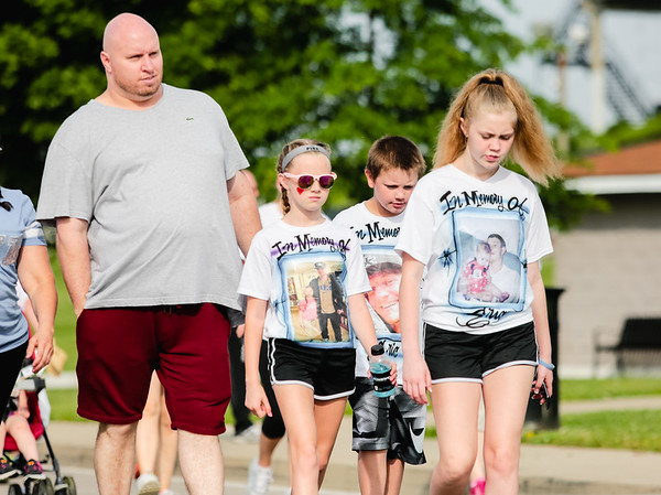 From left, Mallory, 11, Lukas, 9, and Hanna, 14, Kestler, wear shirts honoring their father Eric Kestler, who passed away earlier this year in Louisville. Eric's brother Jason Kestler follows the children as they move through the Stop Addiction Walk in New Albany on Saturday. Staff Photo By Josh Hicks