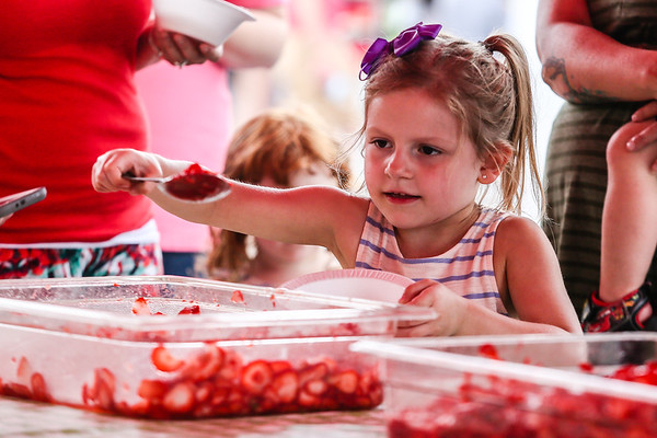 Serinity Dobbins, 5, takes a big scoop of strawberries to pile on top of her shortcake at the Starlight Strawberry Festival on Saturday. Staff Photo By Josh Hicks