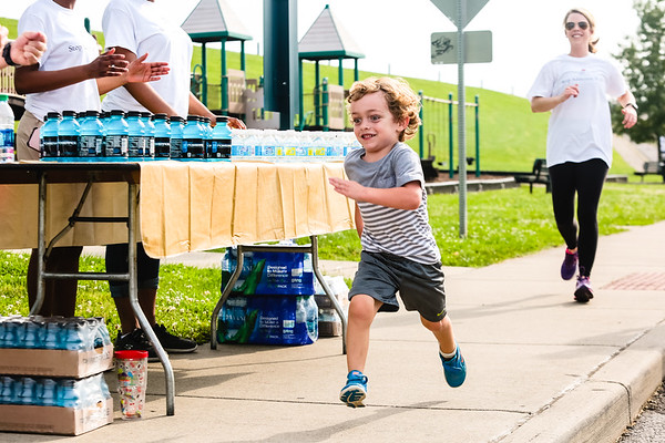 Max Johnson, 5, sprints passed a drink station during the Stop Addiction Walk in New Albany on Saturday. Staff Photo By Josh Hicks
