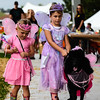Sisters Finley, 6, right, and Farrah Poling, 4, walk their poodle, Liza Jane, before the judges in Monday's Pet Costume Contest at the New Albany amphitheatre. Staff photo by Tyler Stewart