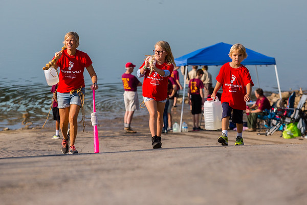 From left, Ruth Ann Snyder, Lucia Bartley, 8, and Townes Bartley, 5, carry heavy jugs of water up the boat ramp on the New Albany riverfront during the Water:Walk.