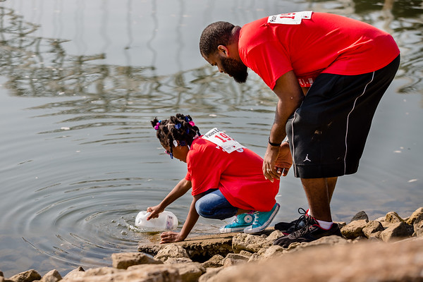Mariah Harris, 9, and her father Jon Harris collect a gallon of water during the Water:Walk on Saturday.