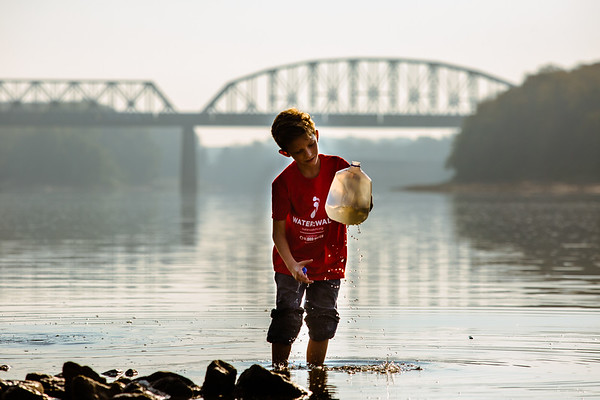 Aiden Sears, 10, who went on to finish first in the 5k walk during the Water:Walk, raises his gallon jug to see how much water he has collected from the Ohio River on Saturday. Staff Photos By Josh Hicks