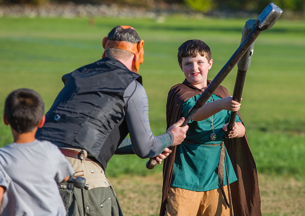 Holden Faith, 10, spars with a masked villian during LARP in the Park on Saturday.