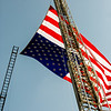 Two firetruck ladders fly the American Flag over Big Four Park during the 9/11 memorial service on Sunday.