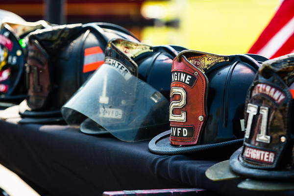Helmets from local fire stations sit on display during the 9/11 memorial service to honor fallen firefighters.