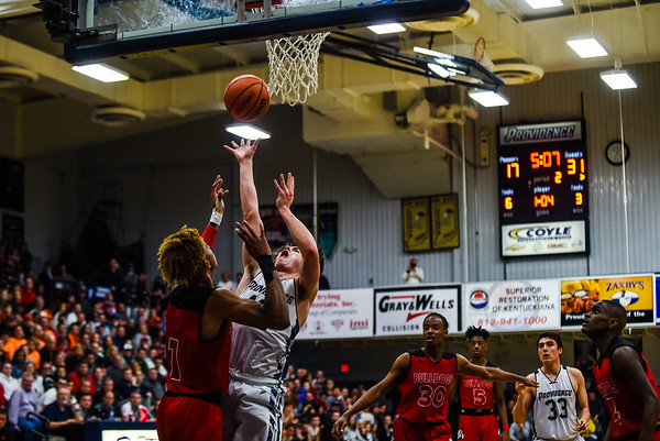 Austin Barnett draws a foul from Romeo Langford during Providence's loss to New Albany on Friday. Staff photo by Tyler Stewart