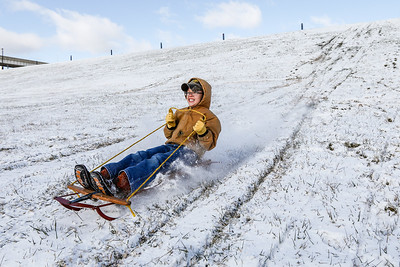 Wade, 10, steers a metal sled from the 1980's down a tall hill along the Ohio River Greenway in New Albany on Saturday.