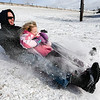 James Gardner and his daughter Jane Gardner, 6, kick up snow as they zip down a hill along the Ohio River Greenway in New Albany on Saturday.