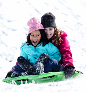 Juliette Garcia, 7, left, and Layla Norris, 11, share a circular sled, spinning down a hill backward in Jeffersonville on Saturday.