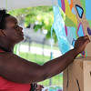 Teaching artist based out of the Mellwood Art Center Marlesha Woods paints a tree during Art on the Parish Green on Saturday. Staff Photos By Josh Hicks