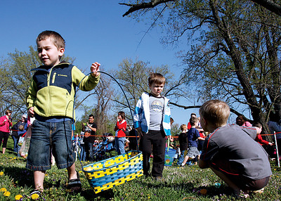 Andrew Reid, 4, and Kaiden Jarboe, 4, head back to their parents after gettin as many Easter eggs as they could at an egg hunt on Saturday at Colgate Park. About 2,000 eggs were laid out for the children. Staff photo by Jerod Clapp