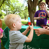5-19-12<br /> Royce Cage, 2, gets a popsicle from his mom who bought them for he and Miley Bradley, 3, at Foster Park near the Little House. The girl scouts from troop 520 were selling lemonade and popsicles. Saturday was national Lemonade Day. Lemonade stands popped up all over town and all over the country organized by the Think Forward Foundation. The idea is to teach kids entrepreneurial skills. More info at indianapolis.lemonadeday.org<br /> KT photo | Tim Bath