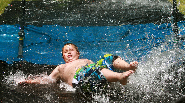 6-13-12<br /> Coleman Stone, 9, slides through the fire hoses set up by The Kokomo Fire Department at Bon Air Park Wednesday afternoon.<br /> KT photo | Kelly Lafferty