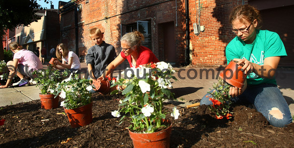 5-19-12<br /> Voluteers plant flowers and other plantings in the downtown area on Saturday morning. Julie Hilligoss with her kids Jeffery Hilligoss and Alyssa Hilligoss plant flowers along the parking lot flowerbeds between Union, Main, Sycamore and Walnut Streets.<br /> KT photo | Tim Bath