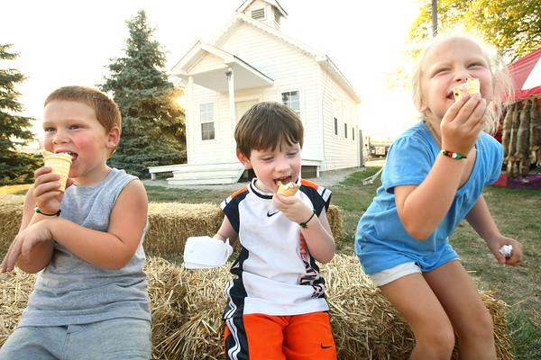 7-11-12<br /> HC Fair rides and food<br /> Hudson Hamilton, 4, Alijah Alexander, 4, and Elle Hamilton, 5, eating ice cream in the Pioneer Village.<br /> KT photo | Tim Bath