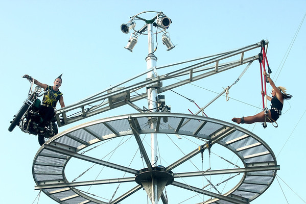 7-10-12<br /> Galaxy Girl Howard Co Fair<br /> Johnny Rocket drives his motorcycle in the air as Galaxy Girl is on a trapeze during the Howard County fair.<br /> KT photo | Kelly Lafferty