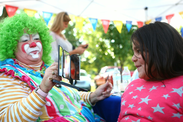 7-17-14<br /> Duck Derby<br /> 6-year-old Jackie Aguilar looks at her face paint in the mirror held by Madonna Johnson, dressed up as Tilli the Clown before the start of the Duck Derby at Kokomo Beach Thursday evening.<br /> Kelly Lafferty | Kokomo Tribune
