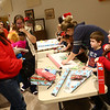 7-year-old Shelby Chase, right, chats with Rebecca Craig as Chase and other members of Girl Scout troop 3995 wrap presents at the Sharing and Caring event at UAW 685 on December 20, 2017.<br /> Kelly Lafferty Gerber | Kokomo Tribune