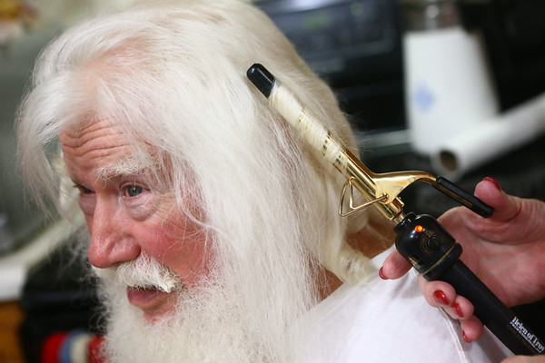 Bill Roe gets his hair curled by his wife, Janice Roe, before the pair goes out as Mr. and Mrs. Claus.<br /> Kelly Lafferty Gerber | Kokomo Tribune