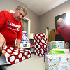 Terry Devine, left, and Tyler Love wrap gifts for Mental Health America's Gift Lift at Shelter Insurance on December 5, 2017.<br /> Kelly Lafferty Gerber | Kokomo Tribune