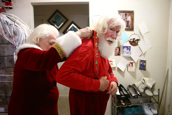 Janice Roe helps her husband Bill Roe with his suspenders as they get dressed and prepare for an outing as Mr. and Mrs. Claus. The Roes have been playing the Clauses for more than 30 years.<br /> Kelly Lafferty Gerber | Kokomo Tribune