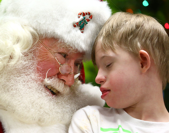 Bill Roe, playing Santa Claus, puts his forehead on Ryder Sheline's forehead as Ryder sits on his lap. The Roes visited Ryder and other students in Bon Air Elementary's Life Skills class earlier in December.<br /> Kelly Lafferty Gerber | Kokomo Tribune
