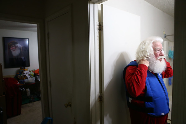 Bill Roe adjusts his cooling vest as he prepares for an outing as Santa Claus. Roe wears a cooling vest with icepacks underneath his heavy Santa suit to help prevent him from becoming overheated. In the bedroom behind him is an award-winning photograph of Bill playing Santa.<br /> Kelly Lafferty Gerber | Kokomo Tribune