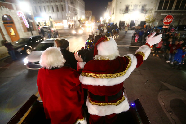 Pulled in a horse-drawn sleigh, Bill and Janice Roe greet children as Mr. and Mrs. Claus as they make their entrance into downtown Kokomo for December's First Friday event.<br /> Kelly Lafferty Gerber | Kokomo Tribune