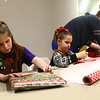 Eliana Carlson, 7, wraps presents along with the rest of her Girl Scout troop 3995 during the Sharing and Caring event at UAW 685 on December 20, 2017.<br /> Kelly Lafferty Gerber | Kokomo Tribune