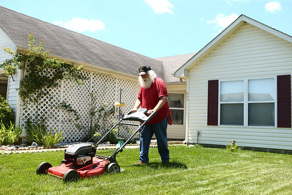 Even as Bill Roe mows his front yard on a hot summer day in June, he wears a red shirt. Bill, a retired Chrysler tool setter, hasn't cut his Santa Claus beard since 2005. <br /> Kelly Lafferty Gerber | Kokomo Tribune