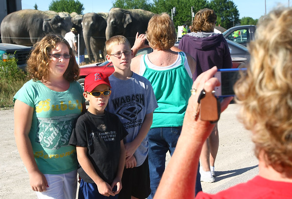 5-30-12<br /> Ringling Bros. and Barnum and Bailey Circus train stopped in Peru to fuel up, fill water and fix a generator. They also let the animals out for exercise and food. Hundreds stopped by the Norfolk Southern train yard to see the elephants on Wednesday. Molly Moore, John Moore and Kallen Kelsheimer hve their photo taken by grandma Cindi Price in front of the elephants.<br /> KT photo   Tim Bath