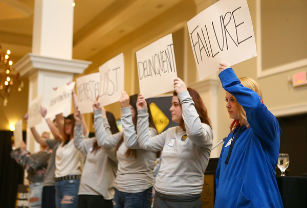 """Jazlyn Brown, right, and other students from The Crossing in Kokomo hold up a cardboard sign with a word that used to describe them, before ripping up the signs and holding up a new sign with a word describing how they've transformed as they share their """"cardboard stories"""" during a celebration banquet on Thursday, April 26, 2018.<br /> Kelly Lafferty Gerber 