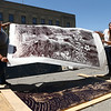 With the help of IUK alumni and visiting artist Tarja Harney, left, Aly Davis, right, lifts her piece that was transferred to paper using a steamroller in downtown Kokomo for IUK's Relief Printmaking class on Thursday, April 26, 2018.<br /> Kelly Lafferty Gerber | Kokomo Tribune