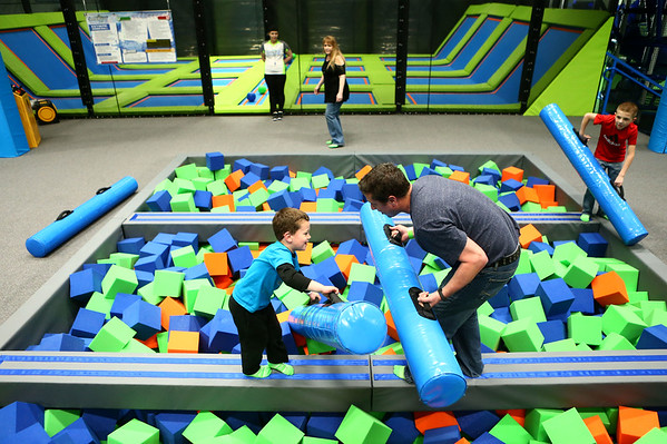 Emerson Chesshir, 4, and his dad Keith Chesshir face off on the battle beam during the opening day of Gravity Trampoline Park in Markland Mall on Friday, April 20, 2018.<br /> Kelly Lafferty Gerber | Kokomo Tribune