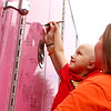 With the help of her mom Jamie Corn, 4-year-old Audrey Corn signs her name on the Pink Heals firetruck after it made a stop at her home on Friday, August 24, 2018. Audrey was diagnosed with leukemia in March.<br /> Kelly Lafferty Gerber | Kokomo Tribune