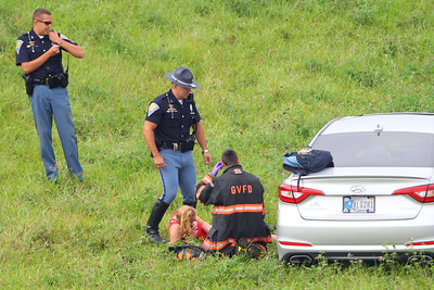Indiana State Police and a Galveston volunteer firefighter with a young lady after she wrecked on Aug. 8, 2018. After a short chase with a trooper in pursuit, the driver ran off the road going down an embankment at Touby Pike and US 31. Tim Bath | Kokomo Tribune