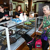 Gail Beaton, accompanied by her service dog Jazzy, takes a look at some of the treats made by Kokomo Area Career Center Culinary Arts students for the Kokomo Confectioners' Company, located at 207 East Superior Street, on its opening day, Tuesday, August 28, 2018.<br /> Kelly Lafferty Gerber | Kokomo Tribune