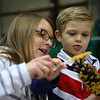 With the help of his mom, Joanne DeMarco, 3-year-old Charlie DeMarco spreads peanut butter over a pinecone to make an ornament during the Russiaville Winter Fest on Friday, November 30, 2018.<br /> Kelly Lafferty Gerber | Kokomo Tribune