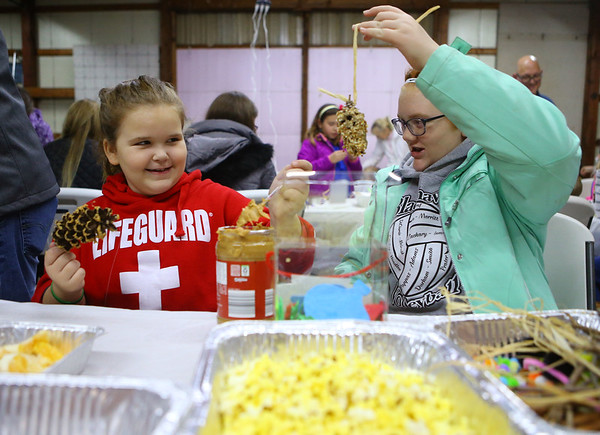 Reese Casler, 7, left, and her cousin Maelei Casler, 12, make pinecone ornaments during the Russiaville Winter Fest on Friday, November 30, 2018.<br /> Kelly Lafferty Gerber | Kokomo Tribune