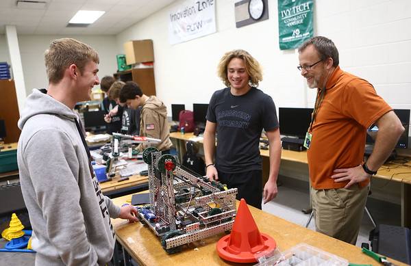 Luke Swartzendruber, left, and Lance VanMatre laugh with Comet Tech robotics instructor John VanMatre, right, as they troubleshoot an issue with the robot on January 10, 2018.<br /> Kelly Lafferty Gerber | Kokomo Tribune
