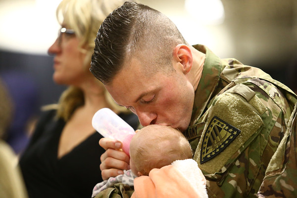 Sfc. Charles McCollum kisses his 4-week-old daughter Charlotte as he feeds her during the 38th Sustainment Brigade departure ceremony on Tuesday, January 2, 2018.<br /> Kelly Lafferty Gerber | Kokomo Tribune
