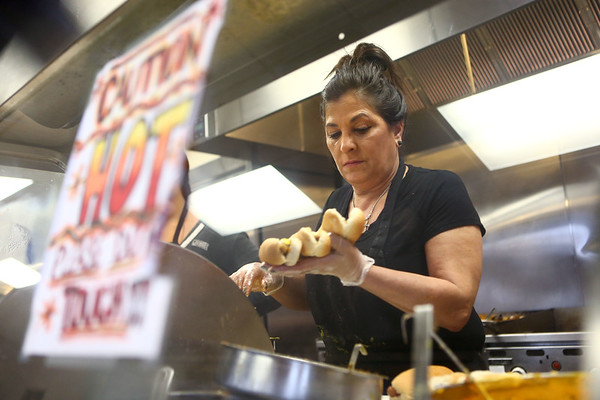 Toula Volikas-Linville prepares coneys and bakes for the lunch crowd at Louie's Coney Island on January 23, 2018. Volikas took over the family business from her Louie, her dad, in the 1980's. Louie's Coney Island is the oldest restaurant in Howard County and it's still in the same family.<br /> Kelly Lafferty Gerber | Kokomo Tribune