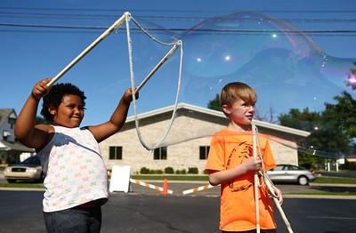 Cody Word, 7, right, watches as 5-year-old Violet Matthews creates a big bubble outside the Kokomo-Howard County Public Library on Friday, July 6, 2018. Kelly Lafferty Gerber | Kokomo Tribune