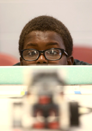 Keiandre Cannon, 12, gets level with the playing field as he watches to see if he programmed his robot correctly to complete its task during the Carver Center robotics team practice on Tuesday, July 3, 2018.<br /> Kelly Lafferty Gerber | Kokomo Tribune