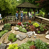 People walk across the arched footbridge over a waterfall to observe the garden of Richard and Mary Ellis during the Garden Stroll on Saturday, June 23, 2018.<br /> Kelly Lafferty Gerber | Kokomo Tribune