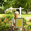 """Susan Jordan holds a framed copy of the music cover of Cole Porter's """"Old Fashioned Garden"""" song as she stands in her garden on June 5, 2018. Porter's step-grandmother, who used to live on the property had a garden that inspired the hit song."""