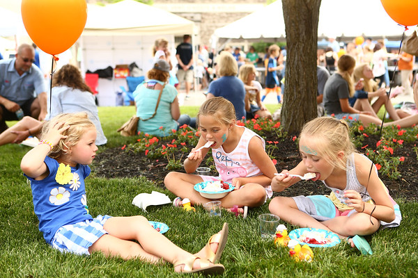 Friends from left: Addy Smith, 4, Raygan McClain, 8, and Isabelle Kucholick, 8, take breaks in between chatting to eat their strawberry shortcake dessert as they sit in front of the Howard County Courthouse during the Strawberry Festival in downtown Kokomo on Friday, June 1, 2018.<br /> Kelly Lafferty Gerber | Kokomo Tribune
