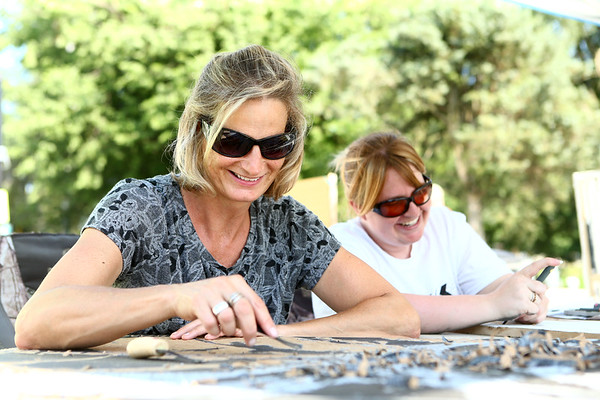Minda Douglas, left, and Lori Brubaker do wood block carving during the Maker City Fair at the Haynes Apperson Festival on Friday, June 29, 2018.<br /> Kelly Lafferty Gerber | Kokomo Tribune